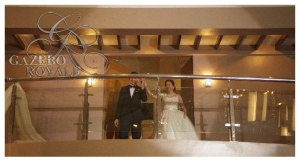 Couple may glance at their guests before going down the staircase